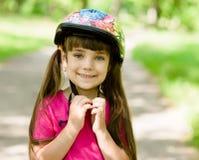 Lilla flickan klär en cykelhjälm arkivbilder