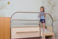 Lilla flickan klättrar på sängen som rymmer ledstången arkivbild