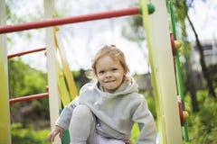 Lilla flickan kl?ttrade p? barn glider p? en lekplats f?r barn och ?r j?tteglad att spela arkivbilder