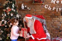 Lilla flickan kommer till Santa Claus, framlägger gåvan för det nya året och kramen Fotografering för Bildbyråer