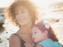 Lilla flickan kramade hennes mamma på solnedgången på stranden Royaltyfri Fotografi