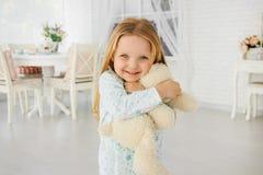Lilla flickan kramar en nallebjörn Leenden sinnesrörelser av lycka björnflicka little leka nalle royaltyfria bilder