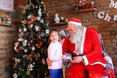 Lilla flickan kramar Santa Claus och gör önskaen för jul i coz Royaltyfri Bild