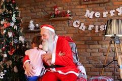 Lilla flickan kramar Santa Claus och gör önskaen för jul i coz Arkivbilder