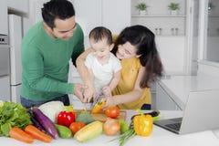 Lilla flickan lär att laga mat med hennes föräldrar arkivbilder