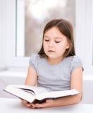 Lilla flickan läser en bok Royaltyfria Bilder