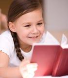 Lilla flickan läser en bok Arkivbild