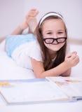 Lilla flickan läser en bok Royaltyfri Fotografi