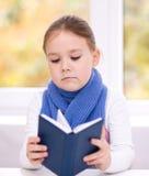 Lilla flickan läser en bok Fotografering för Bildbyråer