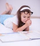 Lilla flickan läser en bok Arkivfoto
