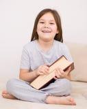 Lilla flickan läser en bok Royaltyfri Foto