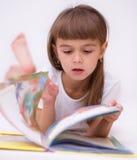 Lilla flickan läser en bok Arkivfoton