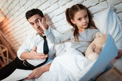 Lilla flickan låter inte hennes fader arbeta Dottern kräver uppmärksamhet av den upptagna fadern royaltyfri foto