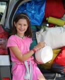 Lilla flickan laddar påsarna i stammen av hennes bil Arkivfoto