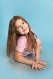 Lilla flickan ligger på en blå bakgrund Fotografering för Bildbyråer