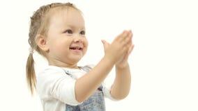 Lilla flickan lyfter henne händer upp bak hennes huvud och spelar Vit bakgrund stock video