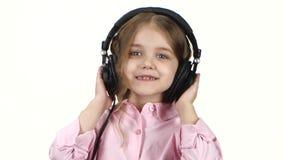 Lilla flickan lyssnar musik på hörlurar, och danser, slut ups stock video