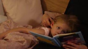 Lilla flickan lyssnar till en saga för läggdags lager videofilmer