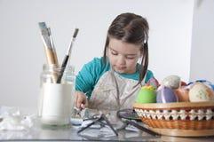 Lilla flickan målar ägg Arkivfoto