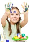 Lilla flickan målar ägg som förbereder sig för påsk Arkivfoto