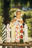 Lilla flickan målar ett staket Arkivbilder