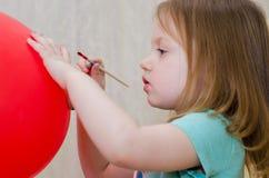 Lilla flickan målar på ballongen royaltyfri fotografi