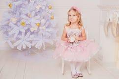 Lilla flickan med blont hår i rosa färger klär i bakgrund för nytt år royaltyfri foto