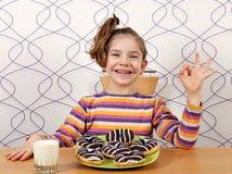 Lilla flickan med chokladdonuts och okhanden undertecknar Royaltyfri Fotografi