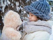 Lilla flickan med den mjuka nallebjörnen i en vinter parkerar fotografering för bildbyråer