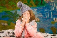 Lilla flickan med den rinnande näsan torkar hennes näsa arkivbild