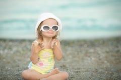 Lilla flickan med Down Syndrome bar exponeringsglas och poserar framsidor royaltyfria bilder