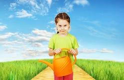 Lilla flickan med en bevattna can står i fältet Royaltyfri Fotografi