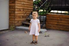Lilla flickan med en iklädd gullig rosa färg för allvarlig blick klär Royaltyfria Foton