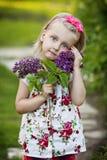 Lilla flickan med en lila bukett i en trädgård Arkivfoton