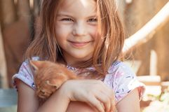 Lilla flickan med en röd kattunge i händer stänger sig upp BESTFRIENDS I royaltyfri bild
