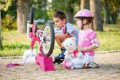 Lilla flickan med en rosa säkerhetshjälm lär hur man fixar cykeln Royaltyfria Bilder