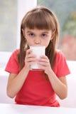 Lilla flickan med ett exponeringsglas av mjölkar Royaltyfri Foto