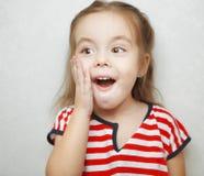 Lilla flickan med förvånat ansiktsuttryck rymmer hennes kind royaltyfria bilder
