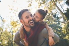 Lilla flickan med fadern har gyckel Förälskelse och kyssar till pappan Royaltyfri Bild