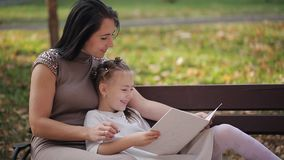 Lilla flickan med fräknar som stället med mamman sitter på en bänk i, parkerar Lycklig familj som tillsammans läser en bok stock video
