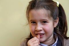 Lilla flickan med framtanden dinglar arkivbilder
