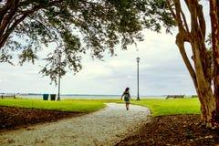 Lilla flickan med lång hårspring bland träd i utomhus- parkerar i charleston med havssikt Arkivbilder