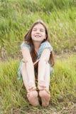 Lilla flickan med långt hår sitter på det gröna gräset Arkivfoto
