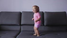 Lilla flickan med lockigt blont hår hoppar på soffan blå kläder menar lyckligt stock video