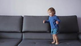 Lilla flickan med lockigt blont hår hoppar på soffan blå kläder menar lyckligt arkivfilmer
