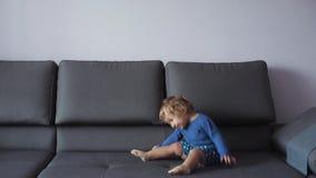 Lilla flickan med lockigt blont hår hoppar på soffan blå kläder menar lyckligt långsam rörelse lager videofilmer