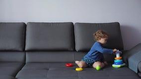 Lilla flickan med lockigt blont hår spelar med bildande leksaker blå kläder menar lyckligt lager videofilmer