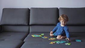 Lilla flickan med lockigt blont hår spelar med pusselleksaker blå kläder menar lyckligt stock video