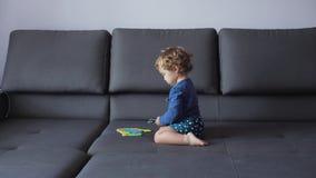 Lilla flickan med lockigt blont hår spelar med pusselleksaker blå kläder menar lyckligt arkivfilmer