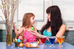 Lilla flickan med mamman målar påskägg för ferien Arkivbild